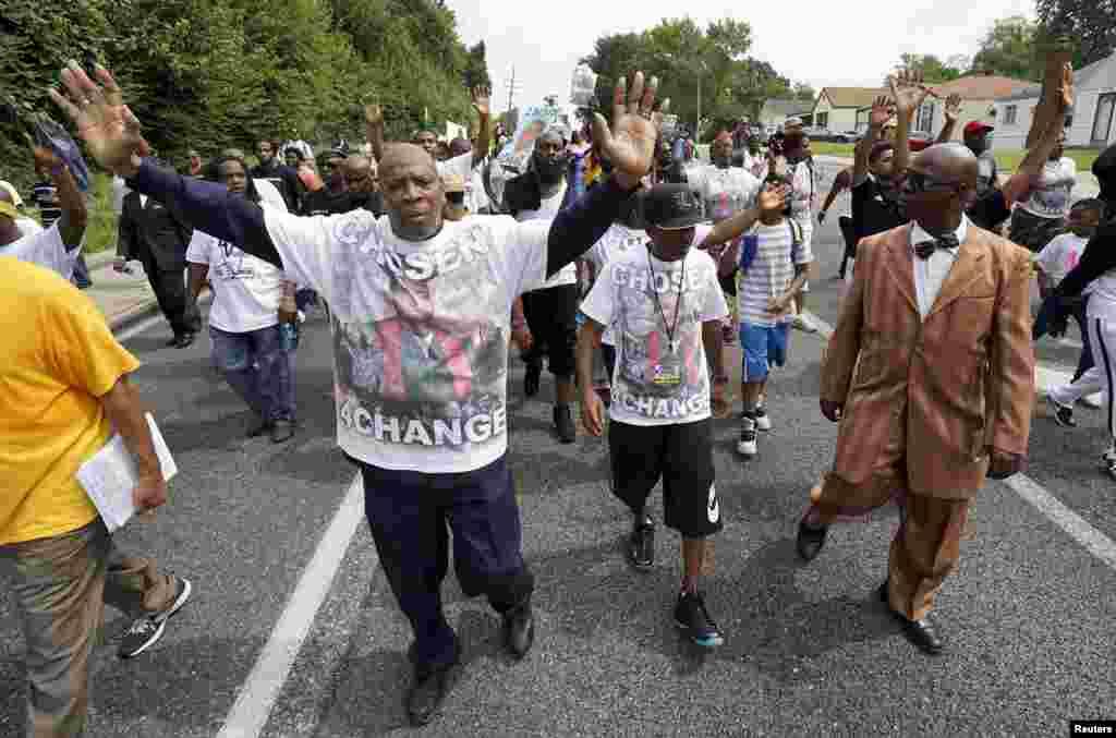 Manifestantes, incluindo Michael Brown Sr. marchando em Ferguson, Missouri, em memória de Michael Brown, 8 de agosto, 2015.