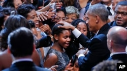 President Barack Obama pats two young girls on the head as he greets guests after speaking at the Congressional Black Caucus Foundation's annual Legislative Conference Phoenix Awards Dinner, Saturday, Sept. 17, 2016, in Washington.
