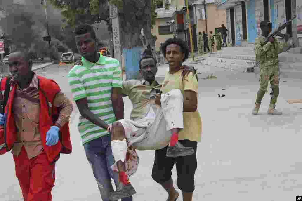 Deux civils somaliens emmènent un blessé de l'attentat à Mogadiscio, en Somalie, le 30 juillet 2017.