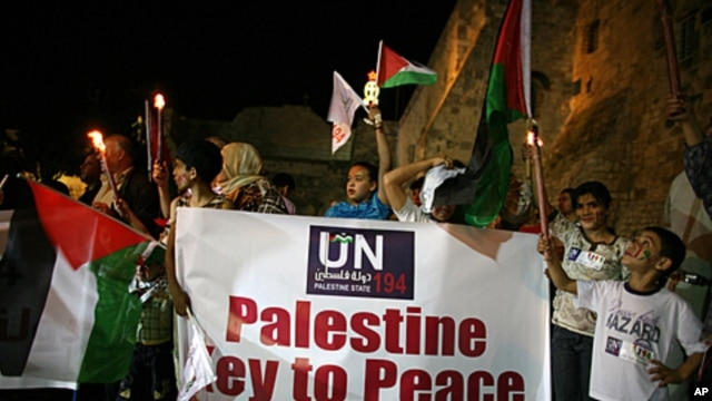 Palestinians take part in a candle light rally outside the Church of the Nativity, in the West Bank town of Bethlehem, to show support for the Palestinian bid for full United Nations membership, September 15, 2011.
