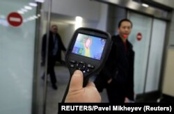 Kazakhstan, Almaty, Kazakh sanitary-epidemiological service worker uses a thermal scanner to detect travellers from China