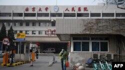 一名戴着口罩的男子走出北京大学人民医院的大门。(2020年2月21日)