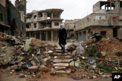 Sumaya Bairuty, 38, an English-language teacher who works in the capital Damascus, walks to her parents house in the war-damaged Bab Dreib neighborhood of Homs, Syria, Jan. 17, 2018.