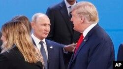 """Президент Дональд Трамп, праворуч, проходить повз президента Росії Володимира Путіна, зліва, коли вони збираються на групову фотографію на початку саміту """"великої двадцятки"""" в Буенос-Айресі, Аргентина, у п'ятницю, 30 листопада 2018 року."""