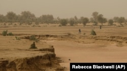 People walk past a dry seasonal riverbed in the Matam region of northeastern Senegal.