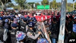 Police block protesters as they gather near a statue of General Aung San during a demonstration in Loikaw, Myanmar, Feb. 12, 2019.