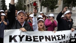 Employees of Greece's health system shout slogans as the banner reads ''Government'' during a protest against government health cuts in Athens, April 17, 2013.