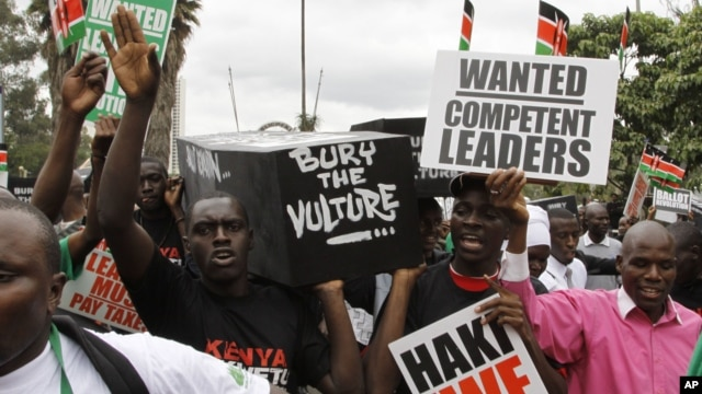 Youth groups protestors carrying replicas of 49 coffins saying bury the vulture seen in Nairobi, Kenya, June 28, 2012.