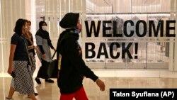 Pengunjung bermasker di pusat perbelanjaan Senayan City saat dibuka kembali setelah ditutup selama berminggu-minggu karena pembatasan skala besar yang diberlakukan untuk mengekang penyebaran wabah virus corona, di Jakarta, Senin, 15 Juni 2020. (Foto: AP/