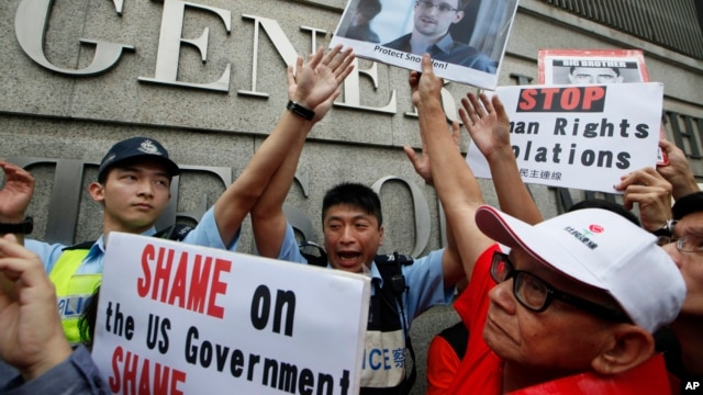 Demonstrators hold signs and a picture supporting Edward Snowden outside the Consulate General of the United States in Hong Kong, June 13, 2013.