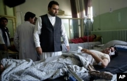 Wounded men lie on their beds in Wazir Akbar Khan Hospital in Kabul after a massive explosion.