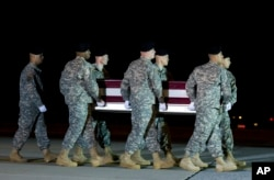 An Army carry team, carries the remains of Army Staff Sgt. Matthew Q. McClintock upon arrival at Dover Air Force Base, Delaware, Jan. 8, 2016.