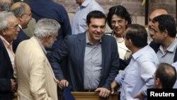 Greek Prime Minister Alexis Tsipras, center, is congratulated by lawmakers after a voting session at the Parliament in Athens, Greece, July 11, 2015.