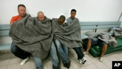 FILE - Cuban migrants huddle together under a blanket, while another sleeps inside a holding cell while the men await processing at the regional U.S. Border Patrol headquarters in Aguadilla, northwestern Puerto Rico, June 13, 2006.