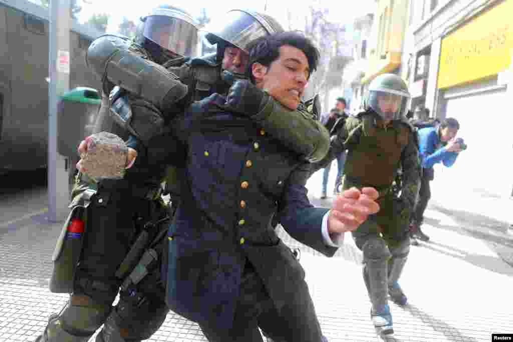 A demonstrator is detained during a rally to demand changes in the education system in Santiago, Chile.