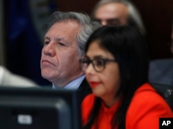 FILE - Secretary General of the Organization of American States Luis Almagro, left, listens to Venezuela's Foreign Minister Delcy Rodriguez as she speaks to the Permanent Council of the Organization of American States in Washington, March 27, 2017.