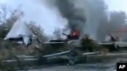 FILE - A Syrian military tank is shown as having caught fire outside Deir Ezzor, Jan. 29, 201.