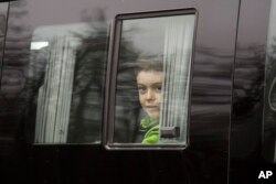 A boy looks through a bus window alleged to be carrying Russian diplomats and their family members who were ordered to leave the US, as they depart from Vnukovo 2 government airport, outside Moscow, Russia, April 1, 2018.
