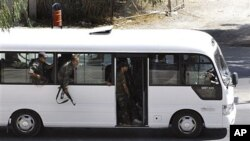 In this citizen journalism image, Syrian security forces lean out of a bus windows as they withdraw from the Damascus suburb of Saqba, Syria, following a campaign of raids and arrests that are part of a nationwide crackdown against protesters calling for