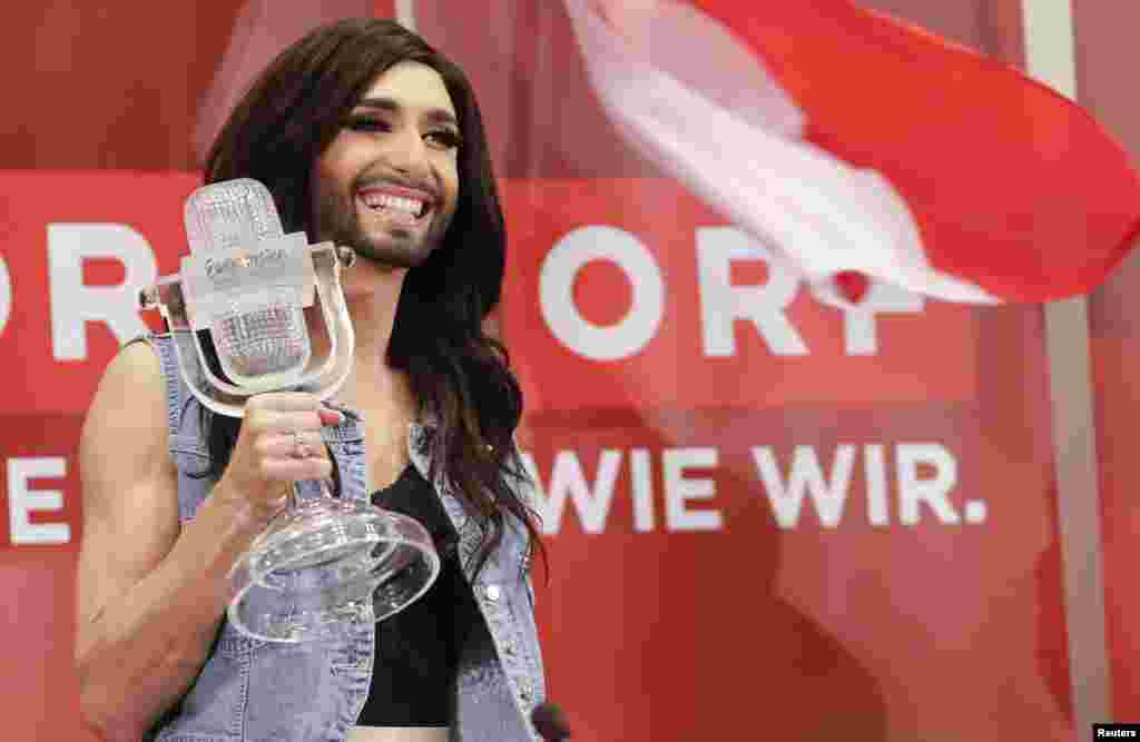 "Austria's Conchita Wurst poses with her trophy before a news conference in Vienna. Wurst, popularly known as ""the bearded lady,"" won the 59th annual Eurovision Song Contest with the James Bond-theme-like ballad ""Rise Like a Phoenix"", before a global TV audience of about 180 million people in 45 countries."