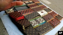A vendor tries to prevent photographs being taken of fake Louis Vuitton and Coach brand purses she was selling on a street in Beijing.