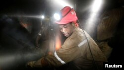FILE - Miners work deep underground at Sibanye Gold's Masimthembe shaft in Westonaria, South Africa, April 3, 2017.
