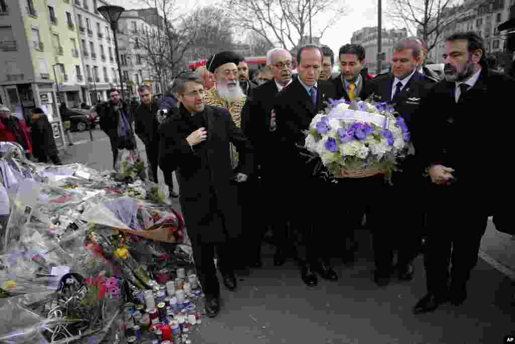 Jerusalem Mayor Nir Barkat, center, and Israeli Chief Rabbi Shlomo Amar, second left, lay a wreath of flowers at the kosher grocery where Amedy Coulibaly killed four people in a terror attack, in Paris, Jan. 21, 2015.