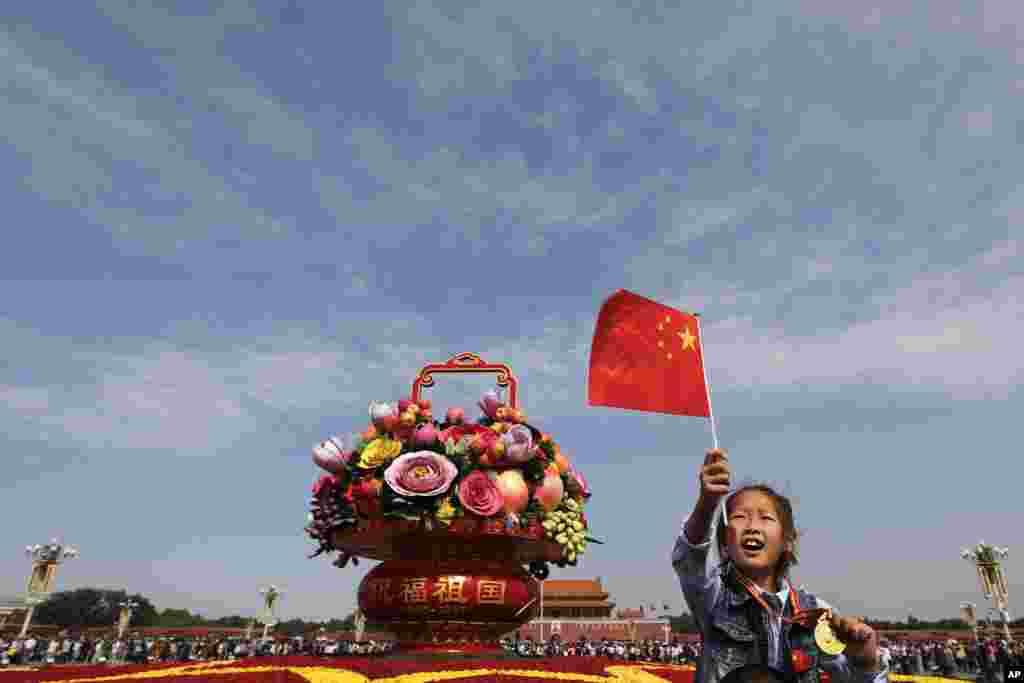ក្មេងស្រីចិនម្នាក់អង្គុយនៅលើស្មាឪពុករបស់នាងនៅក្បែរកន្ត្រកយក្សតែតុបតែងជាមួយនឹងផ្កា និងផ្លែឈើដែលដាក់តាំងនៅទីលាន Tiananmen នៅថ្ងៃបុណ្យឯករាជ្យជាតិរបស់ចិន។