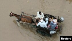 Keluarga Pakistan naik gerobak yang ditarik kuda untuk mengarungi banjir di Lahore (4/9).