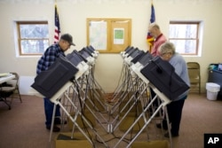 Voters cast their ballots in the primary election Tuesday, March 15, 2016, in Chesterville, Ohio. Voters in five states are making their choices in party primaries. (AP Photo/Matt Rourke)