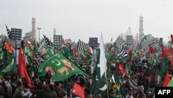 Para pendukung Gerakan Demokratik Pakistan (PDM), mengibarkan bendera dalam unjuk rasa anti-pemerintah di Lahore, Ibu Kota Pakistan, Minggu, 13 Desember 2020. (Foto: Arif Ali/AFP)