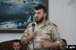 FILE - Zahran Alloush, head of the Army of Islam Syrian rebel group, speaks during the wedding of a fighter in the group in the rebel-held town of Douma, on the eastern edge of Damascus, Syria, July 21, 2015.