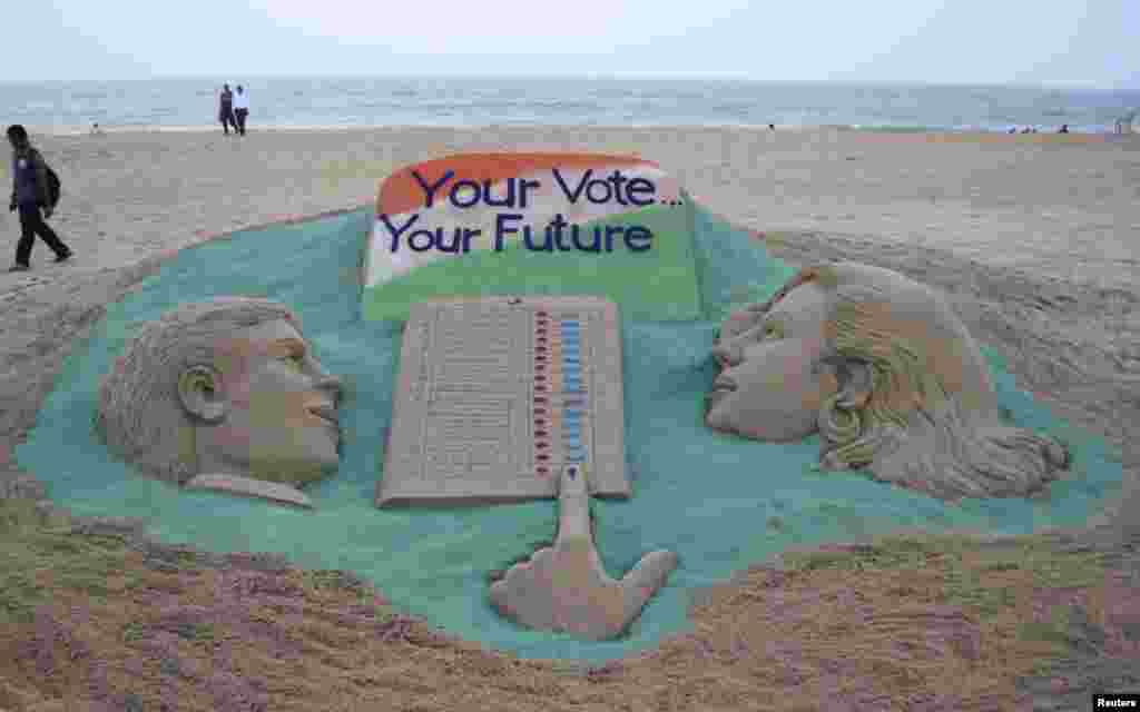 A visitor walks next to a sand sculpture on elections made by Indian sand artist Sudarshan Pattnaik at a beach at Puri in the eastern Indian state of Odisha. Around 815 million people have registered to vote in the world's biggest election.