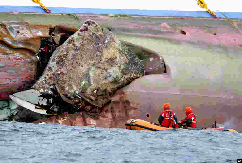 Firefighters on a dinghy look at a rock emerging from the side of the ship on Sunday. (AP)