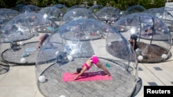 "Support bubbles, not real ""bubbles,"" are small groups of people from two households that socialize together. Here, people take an outdoor yoga class by LMNTS Outdoor Studio using a real half bubble, or dome, to prevent the spread of COVID-19 in Toronto, Canada June 21, 2020."