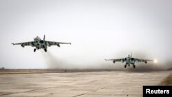 FILE - Sukhoi Su-25 jet fighters take off during a drill at the Russian southern Stavropol region, March 12, 2015.
