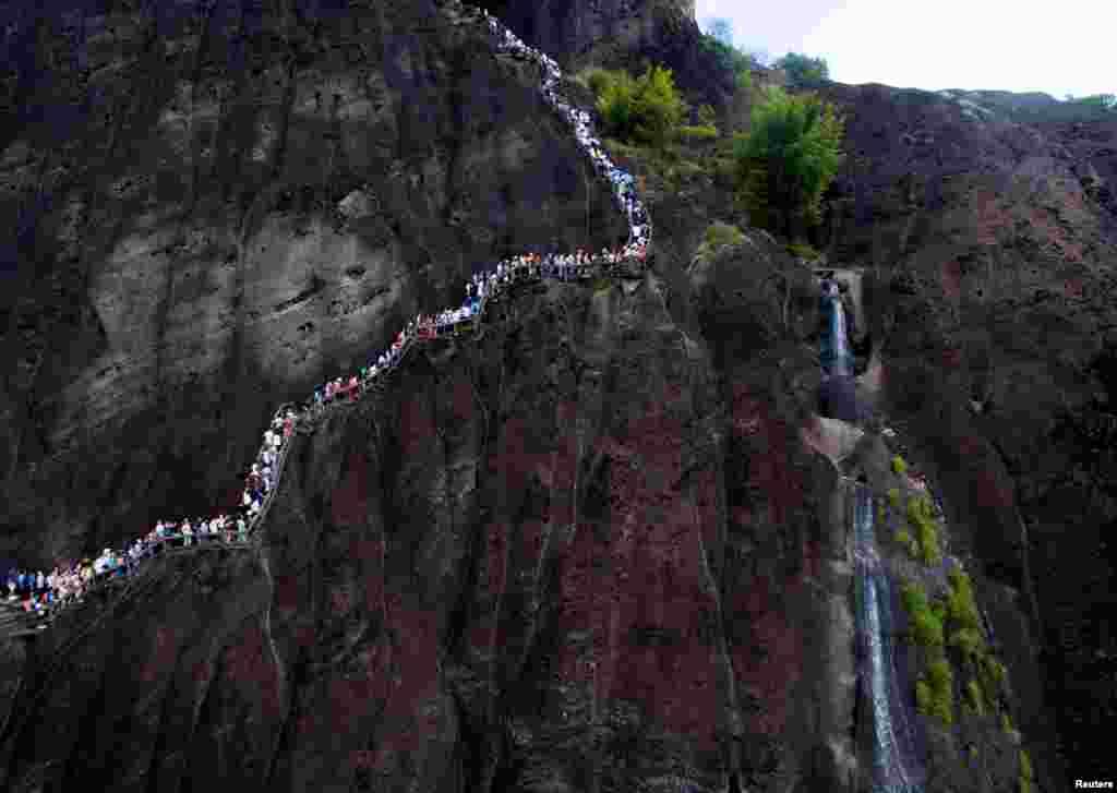 Para pengunjung berjalan mengelilingi pegunungan Wuyi, di kota Nanping, Fujian, China.