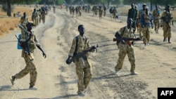 Sudan People's Liberation Army (SPLA) soldiers walk on a road inear Bor, in Jonglei state, on Jan. 31, 2014.