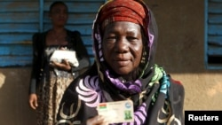 Hauwa Bonkougou, 58 ans, montre sa carte d'électrice dans un bureau de vote de Ouagadougou, le 29 novembre 2015. (REUTERS/Joe Penney)