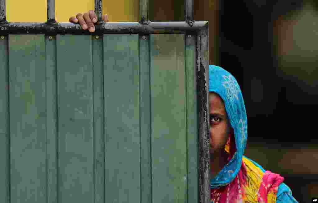 A Sri Lankan Muslim woman looks out on the street in Aluthgama, 50 kilometers (31.25 miles) south of Colombo. At least three Muslims were killed after a right-wing Buddhist group with alleged state backing clashed with Muslims in southwestern Sri Lanka, a government minister said.