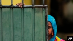 FILE - A Sri Lankan Muslim woman looks out on the street, in Aluthgama, town, 50 kilometers (31.25 miles) south of Colombo, Sri Lanka.