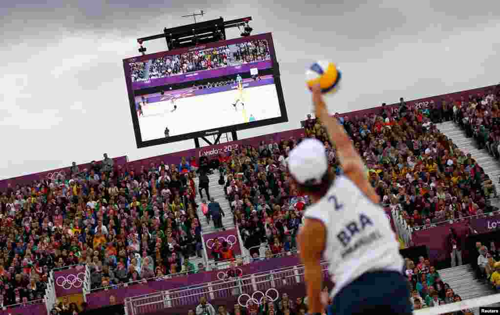 Brazil's Emanuel serves against Poland's Mariusz Prudel and Grzegorz Fijalek during their men's quarterfinals beach volleyball match.