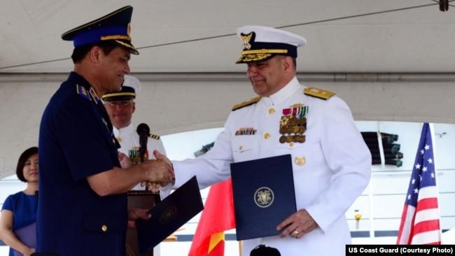 Trung tướng Nguyễn Quang Đạm, Tư lệnh Cảnh sát Biển Việt Nam, và Chuẩn đô đốc Tuần duyên Hoa Kỳ Michael J. Haycock, trợ lý tham mưu trưởng về quân dụng và cán bộ chuyên trách quân dụng, tại lễ chuyển giao tàu tuần duyên trọng tải cao ở Honolulu, Hawaii, tháng Năm năm ngoái.