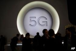 ຜູ້ຄົນກຳລັງພາກັນຢືນຢູ່ ໃກ້ໆກັບເຄື່ອງໝາຍ 5G ລະຫວ່າງການວາງສະແດງ ຂອງສະພາອຸບປະກອນທີ່ບໍ່ໃຊ້ສາຍ ຢູ່ນະຄອນບາເຊໂລນາ ປະເທດສະເປນ.
