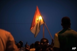 A protester holds a Burkina Faso national flag during a protest against a recent coup in Ouagadougou, Burkina Faso, Sept. 21, 2015.
