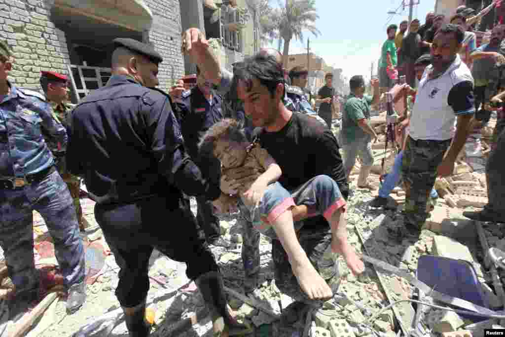 A man carries an injured child found in the rubble after an Iraqi Sukhoi jet accidentally dropped a bomb in Ni'iriya district in Baghdad, Iraq, killing at least five people and destroying several houses.
