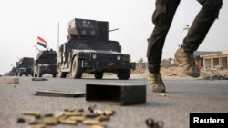 An Iraqi special forces soldier runs as other drive in armored vehicles on a road near Mosul, Iraq, Oct. 25. 2016.