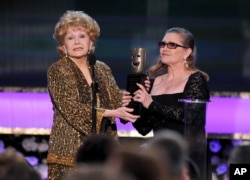 FILE - Carrie Fisher presents Debbie Reynolds with the Screen Actors Guild life achievement award at the 21st annual Screen Actors Guild Awards at the Shrine Auditorium, Jan. 25, 2015, in Los Angeles.