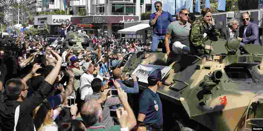 """Cast members Sylvester Stallone (L), Dolph Lundgren (2ndL), Harrison Ford (2ndR) and Jason Statham pose on a tank as they arrive on the Croisette to promote the film """"The Expendables 3"""" during the 67th Cannes Film Festival in Cannes."""