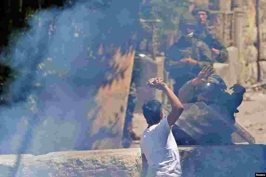 បាតុករប៉ាឡេស្ទីនម្នាក់គប់ដុំថ្មទៅកាន់ទាហានអ៊ីស្រាអែល ក្នុងពេលធ្វើការតវ៉ានៅទីក្រុងHebron នៅតំបន់ West Bank ដែលកាន់កាប់ដោយអ៊ីស្រាអែល។